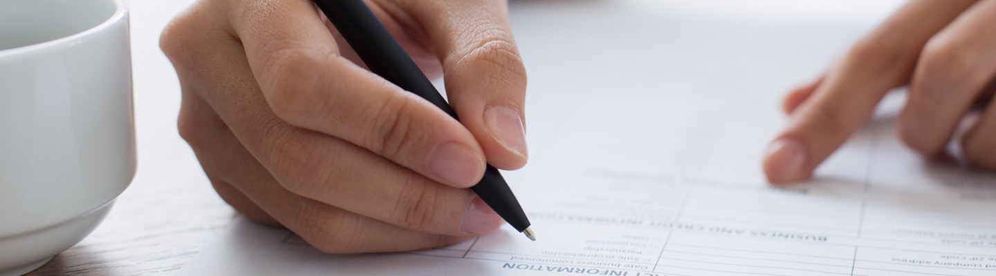 Close up of a person signing form